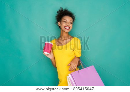 Happy mulatto girl with shopping bags and take away coffe cup. Excited shopaholic at turquoise sudio background with copy space