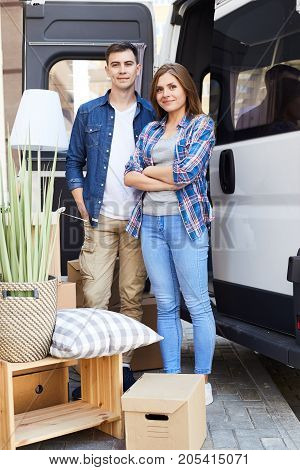 Portrait of smiling young couple, man and woman, posing looking at camera standing next to moving van with cardboard boxes outdoors