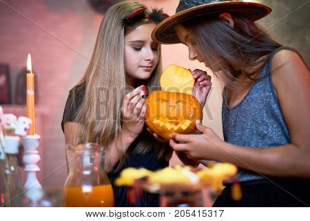Inquisitive little friends in costumes opening jack-o-lantern to put candy inside while enjoying party time together at Halloween