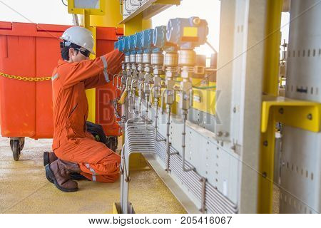 Instrument technician troubleshooting on pressure transmitter on oil and gas wellhead platform.