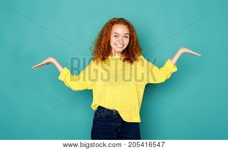 Young smiling puzzled woman with arms out. Asking what is problem, who cares, so what, I don't know on blue background.