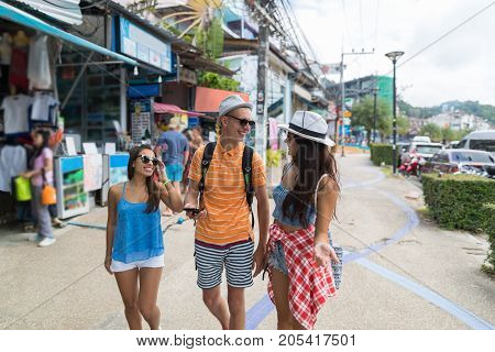 Group Of Tourists Walking Street Of Asian City Together Looking For Right Direction In Mobile Phone Young Cheerful People On Vacation In Asia