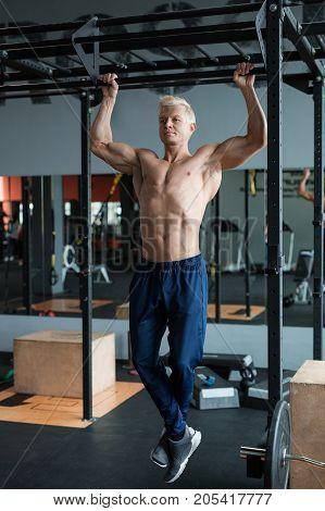 Muscular athlete man making Pull-up in gym. Bodybuilder training in fitness club showing his perfect muscles