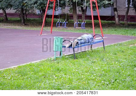 The homeless man sleeps on a bench in the playground. Russia. Moscow region