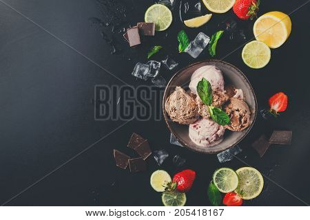 Portion of assorted ice cream scoops in bowl with strawberry, lemon and orange slices and mint on black background top view. Delicious cold sweet dessert, copy space