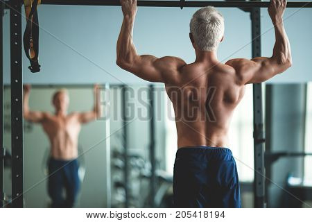 Muscular athlete man making Pull-up in gym. Bodybuilder training in fitness club showing his perfect back and shoulder muscles. Toned image.