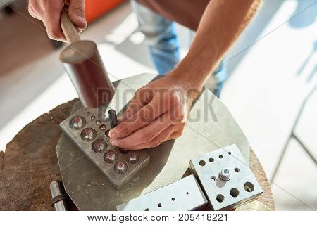 Top view closeup  of young man working with metal in  workshop, forming it with mallet hammer on work station with different tools