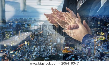 the posture clapping hand of people in business suite with overlay of modern nightcity