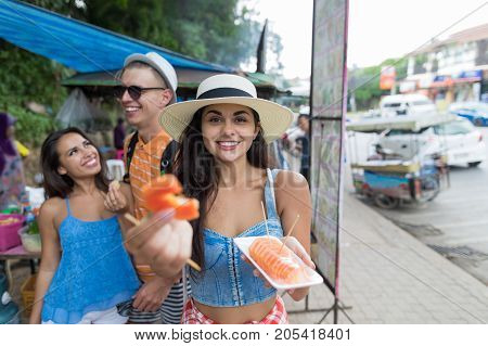 Group Of Tourists Eat Fresh Tropical Fruits Walking Of Asian City Cheerful Young People On Vacation Together Holiday And Communication Concept