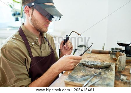 Side view portrait of young man holding small gas torch and welding tools while working with metal against shabby wooden workstation