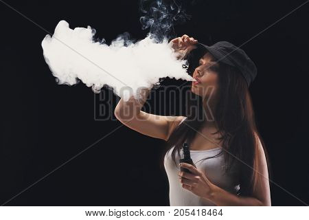 Young woman in a cloud of vape smoke on black background. Hipster girl in cap blowing a cloud of smoke on black background. Nicotine free smoking and vapor concept, copy space