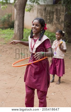 PONDICHERY PUDUCHERY INDIA - SEPTEMBER 04 2017. Young child with uniform plays With Hula Hoop In the school outdoor as a sport.
