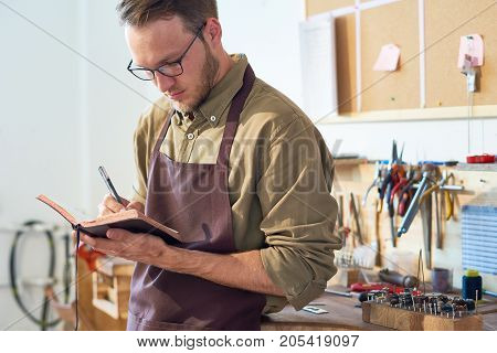 Portrait of young craftsman drawing sketches holding open book while standing in workshop against table with tools