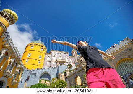 Bottom view of happy woman with open arms at Pena Palace in sunny day. Pena Castle is a Unesco Heritage and one of Seven Wonders of Portugal. Female tourist enjoys of most visited attraction of Sintra
