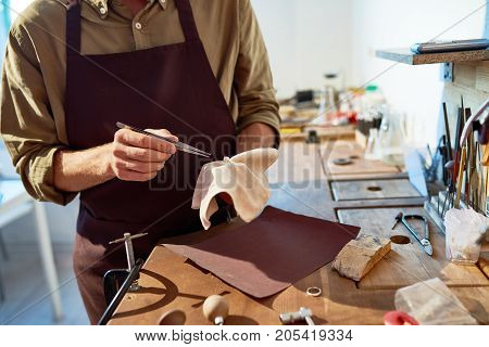 Mid section portrait of unrecognizable jeweler finishing silver ring with precious stone in workshop