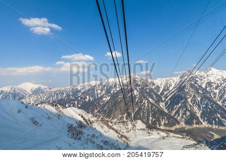 Cable car line going to Tateyama Kurobe Alpine Route on the snow mountains wall Beautiful landscape the view on Tateyama Japanese Alps with blue sky background. Toyama city Japan
