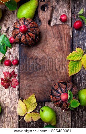 Jack-o-lantern Around Empty Cutting Board On Wooden Background. Autumn Concept. Halloween. Top View.