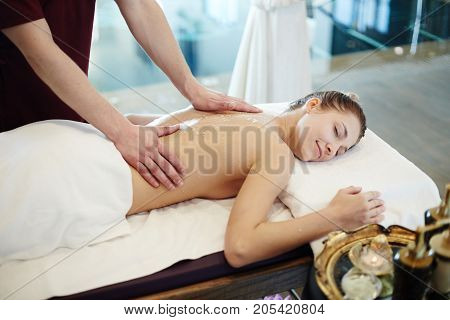 Portrait of blissful young woman enjoying massage in SPA center, lying on massage table with eyes closed and smiling