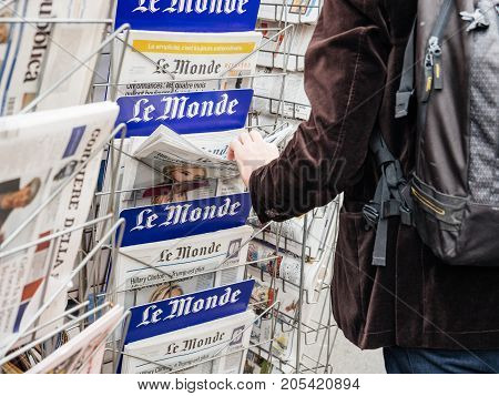PARIS FRANCE - SEP 23 2017: Man buying latest French Le Monde newspaper from press kiosk to read latest news scandals and journalistic investigation