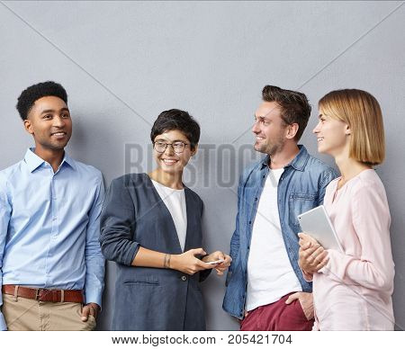 Four Mixed Race People Or Creative Workers Meet Together, Have Intriguing Discussion, Share Their Id