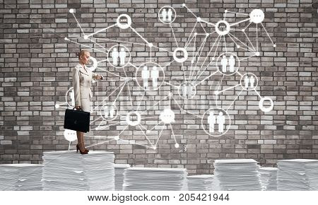 Business woman in suit standing on pile of documents with social network structure on background. Mixed media.
