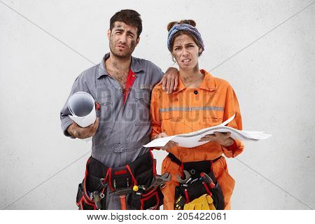 Young Overworked Male And Female Builders Look With Gloomy Expressions, Have No Desire To Work Any M