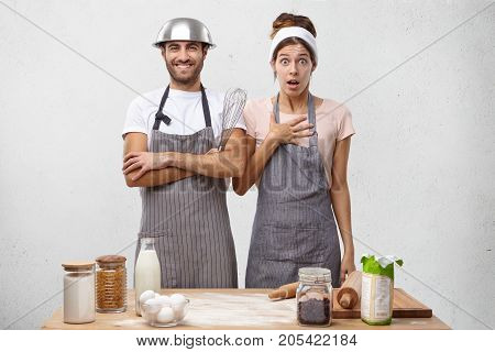 Busy Female Cooker Look Shocked As Has Much Work And His Colleague Foolishes, Wears Bowl On Head, Re