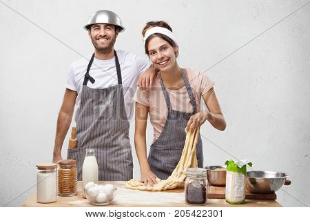 Horizontal Portrait Of Busy Domestic Woman Kneads Dough For Baking Tasty Jelly Roll, Looks Happily A