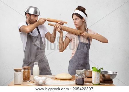 Kitchen Being Battlefield For Two Cookers Who Fight With Utensils. Funny Female And Male Foolishes A
