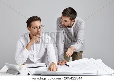 Two Design Workers Brainstrom Together: Young Attractive Male Tries To Persuade His Serious Boss To