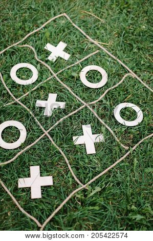 entertainment, amusement, outdoor conept. there is popular game called tic tac toe created with help of few ropes forming squares right on the grass and xs and os made out of paper