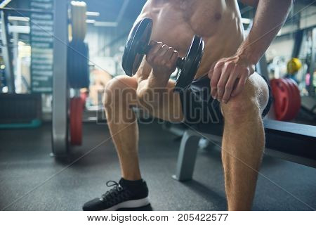 Unrecognizable bodybuilder flexing muscles with dumbbells while having intensive training at spacious gym