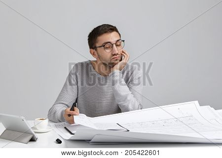 Puzzled Creative Male Engineer, Being Tired After Creating New Drawings Or Blueprint, Is Deeply In T