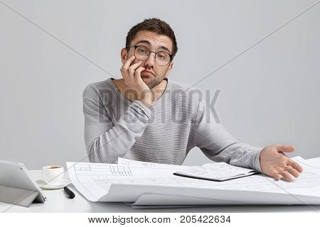 Attractive Young Male Designer Wears Loose Sweater And Big Spectacles, Feels Bored As Works Alone At