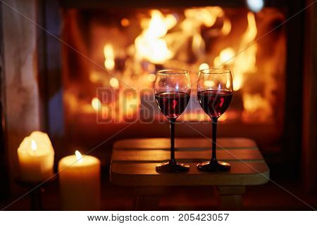 Two Glasses Of Red Wine Near Fireplace