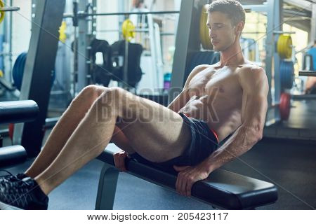 Handsome young athlete with muscular bare torso doing sit ups while having workout at spacious gym, full length portrait