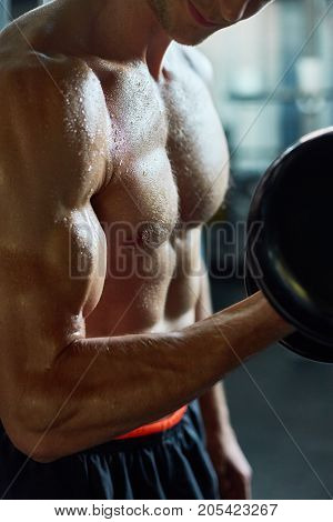 Close-up shot of sporty young man pumping up muscles with dumbbells while having intensive workout at gym