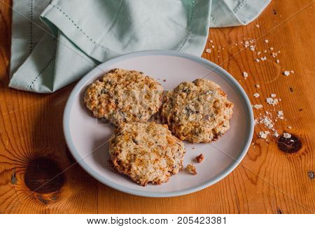 Homemade sweet and crunchy oat meal cookies on rustic bright wooden kitchen table with oats and blue cloth - Food background