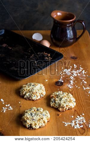 Home baked oats and date cookies on rustic wooden table with egg shell jug and baking tin in background. Vertical photo with copy space