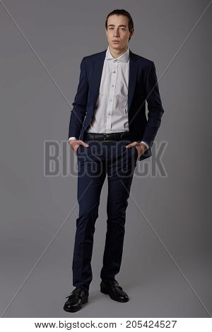 Business fashion man wearing blue suit with white shirt. Studio shot against grey