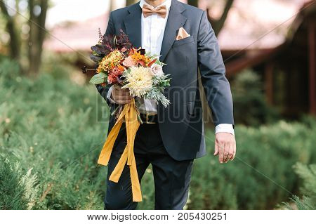 fashion, fall, wedding concept. young handsome man wearing ravishing black suit for fiance with white shirt and charming bow tie, holding glorious bunch of flowers and going ahead purposefully