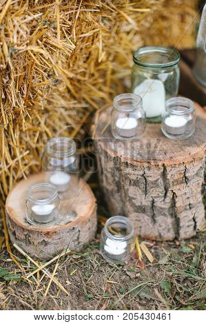 feast design, autumn, country style concept. sparkly glass jars of different sizes used as original candle holders placed on the ground with hay and two twxtured wooden tree stumps