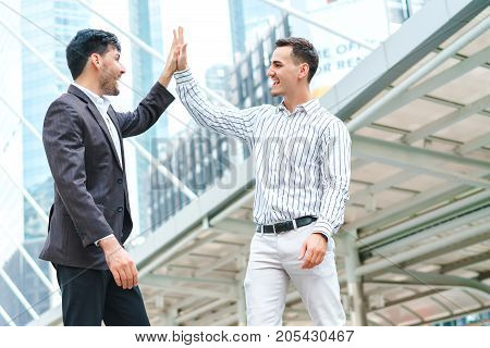 Happy business team making high with clapping their hands in the outdoor teamwork and happy cooperation concept feeling successful.