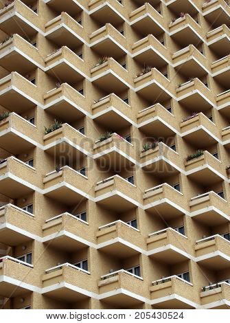 large highrise modern apartment building with large number of repeating geometric balconies in stone yellow colors