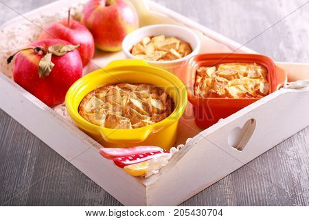Apple puddings in small tins on tray