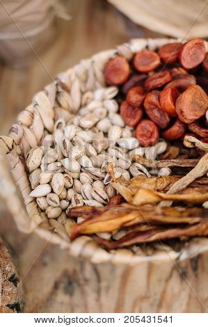 food, healthy lifestyle, gourmet kitchen concet. close up of wickerwork picnic hamper with different delicious snakes such as pistachio nuts, dried apricots and bean sprouts
