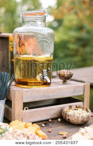 food, refreshment, drinks concept. in the big transparent glass jar with special silver spigot there is yellow lemonade nearby with different tasty snackes like nuts