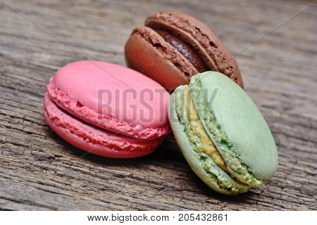 Colorful macaroons on wooden background close up