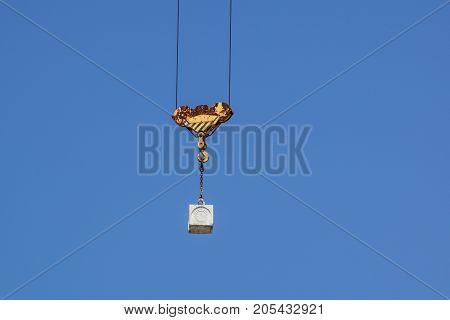 Yellow crane hook on a blue sky .