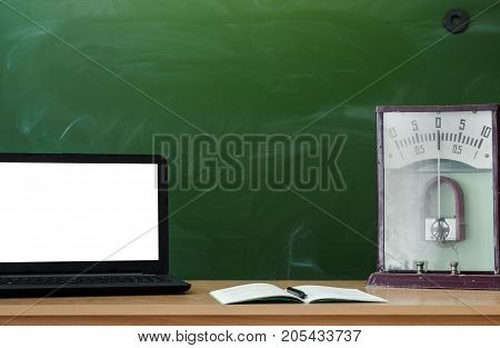 Teacher or student desk table on school blackboard background. Education background. Mockup education concept. Laptop with blank screen copybook and education model of voltmeter on the table.